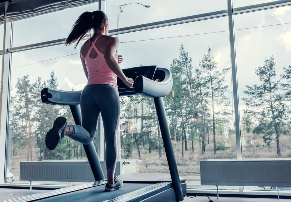 young sports woman is working out in gym - Signs You're Overdoing Cardio