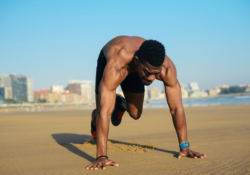 Fit man doing Mountain climbers exercise at the beach - HIIT vs LIIT