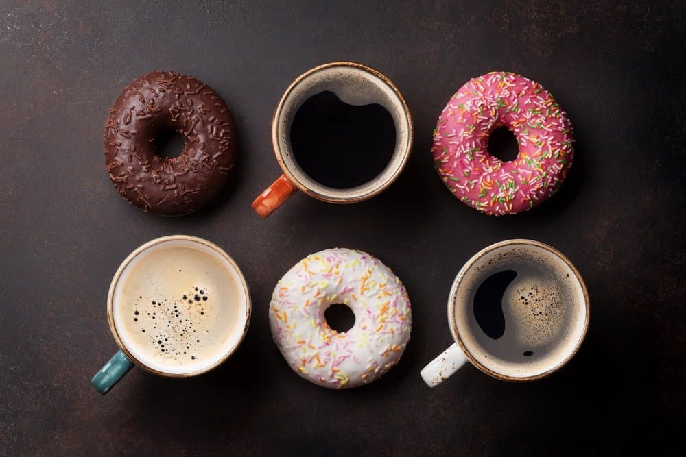 Coffee cups and colorful donuts on stone table. Top view - Top 10 Ways to Weight Loss