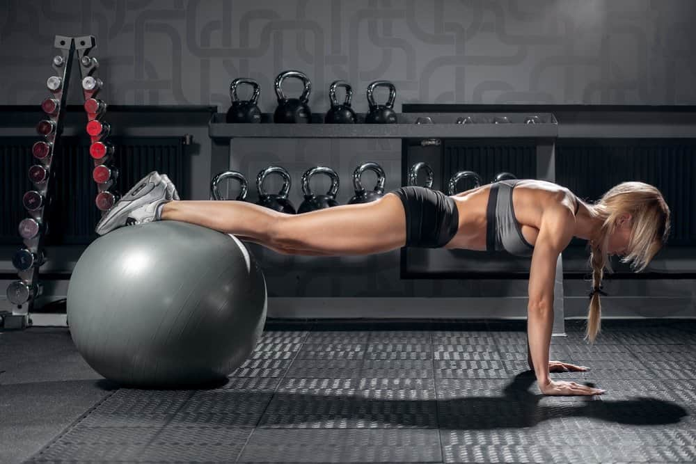 young sporty woman doing fitness exercise plank in gym interior with fit ball - Amazing Facts About Fitness