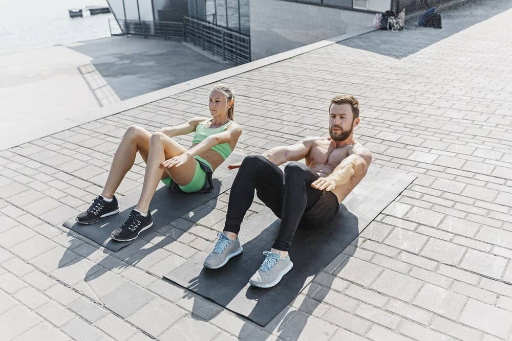 Fit fitness woman and man doing fitness exercises outdoor at city background. the best abdominal muscle press in the world. Female and male sports models exercising in summer at morning. - Amazing Facts About Fitness
