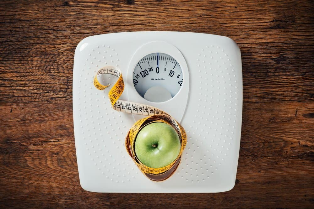Green apple wrapped in a tape measure on a white scale, wooden surface on background, dieting and weight loss concept - Top 10 Ways to Weight Loss