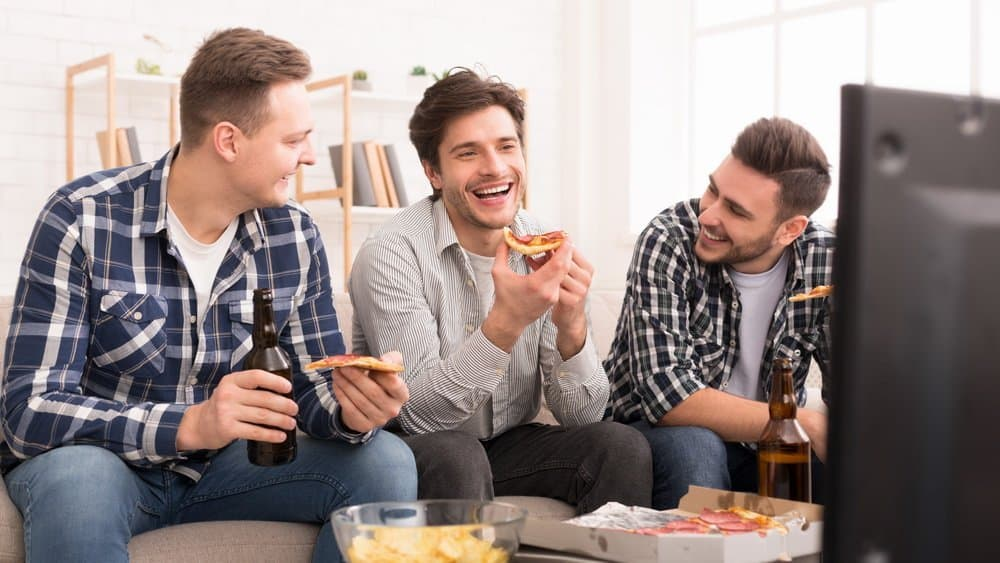 Friends eating pizza and talking, watching tv at home - Top 10 Ways to Weight Loss