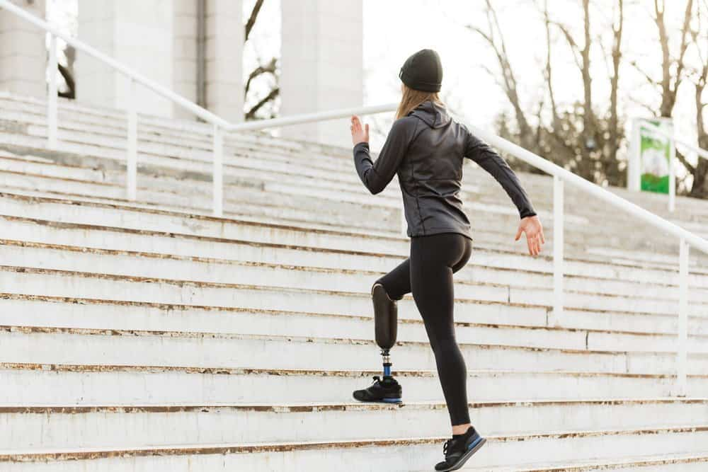 Image from back of energetic disabled girl with prosthetic leg in sportswear working out and running at the stairs in stadium - Top 10 Ways to Weight Loss