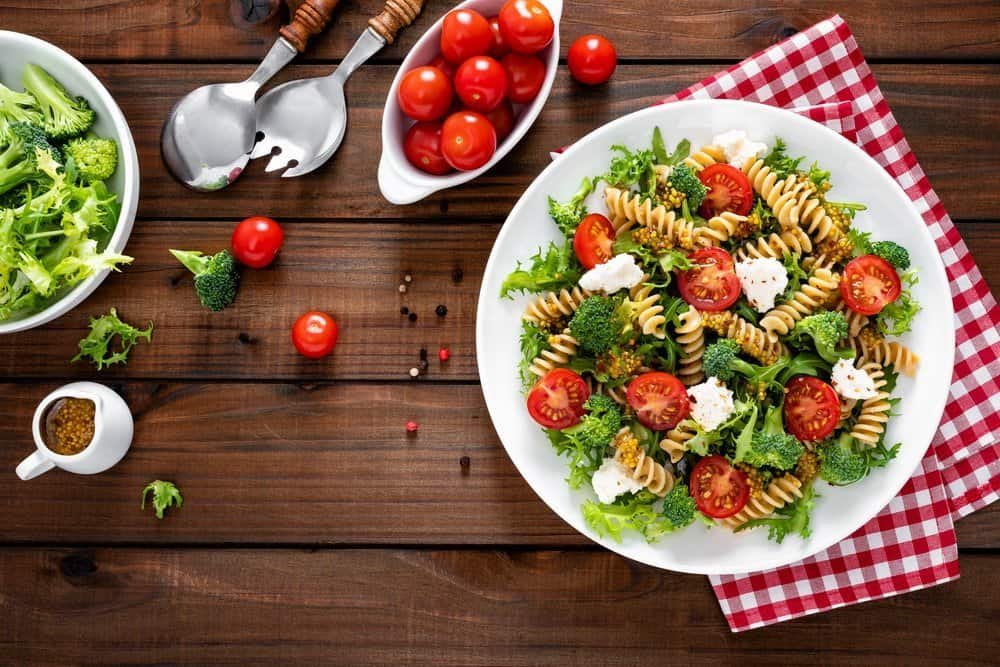 Italian pasta salad with wholegrain fusilli, fresh tomato, cheese, lettuce and broccoli on wooden rustic background. Mediterranean cuisine. Cooking lunch. Healthy diet food. Top view - Top 10 Ways to Weight Loss