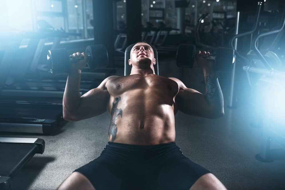 Muscular male bodybuilder training with dumbbells in sport gym. Bodybuilding workout. Power lifting - Amazing Facts About Fitness