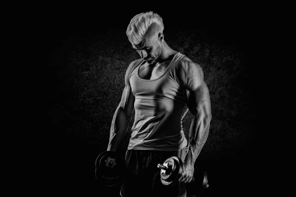 man posing while lifting dumbells - Best Strength Training Workout