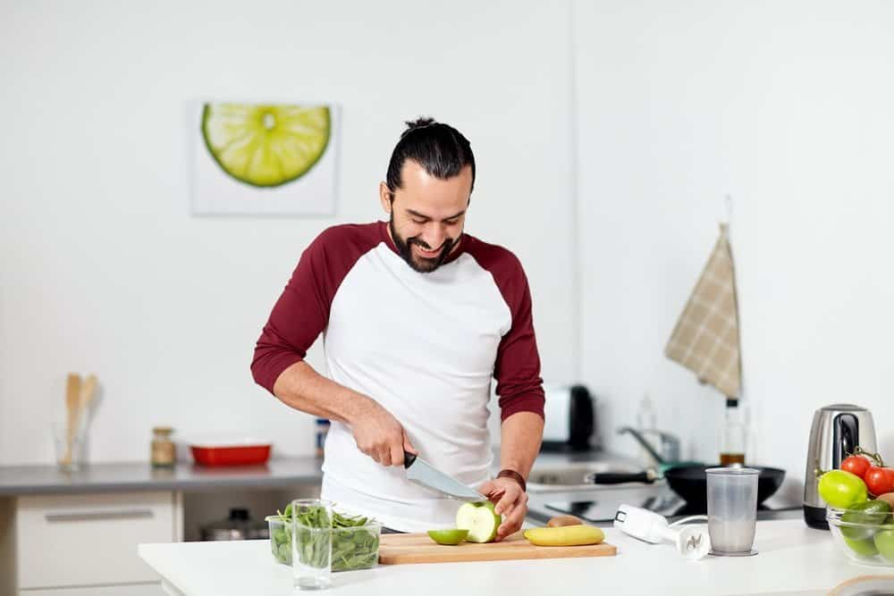 healthy eating, vegetarian food, diet and people concept - happy young man with blender and fruits cooking at home kitchen - Top 10 Ways to Weight Loss