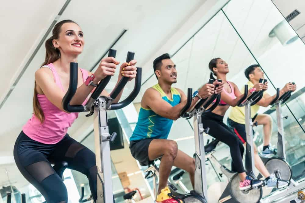 Cardio workout at indoor cycling group - How to Boost Your Body's Fitness Level and Avoid The Risk of Injury. The Ultimate Guide in Cross-Training.