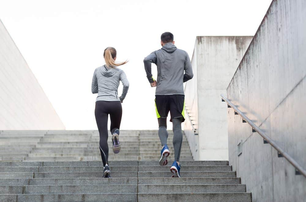 Couple running on city stairs - How Frequently Should a Beginner Exercise Running to Achieve Best Results for the Body and Avoid Injuries Explained