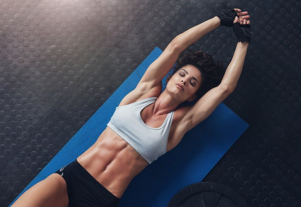 Fitness woman exercising on yoga - Different Body Parts - How to Boost Your Body's Fitness Level and Avoid The Risk of Injury. The Ultimate Guide in Cross-Training.