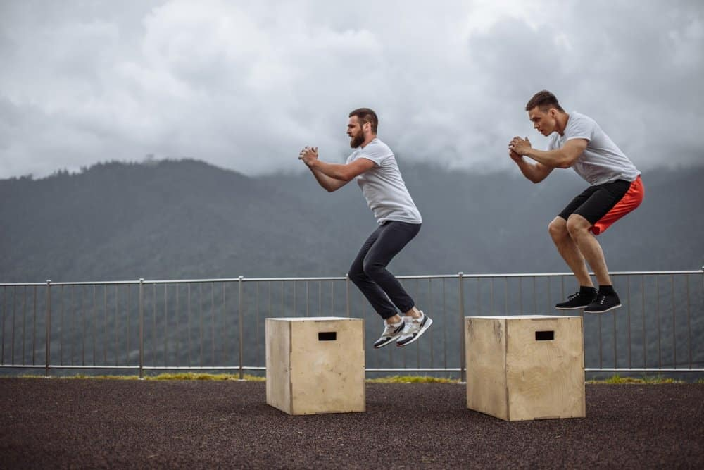 Two young male friends doing extreme box jumps - Plyometrics Workout - How to Boost Your Body's Fitness Level and Avoid The Risk of Injury. The Ultimate Guide in Cross-Training.Two young male friends doing extreme box jumps - Plyometrics Workout - How to Boost Your Body's Fitness Level and Avoid The Risk of Injury. The Ultimate Guide in Cross-Training.