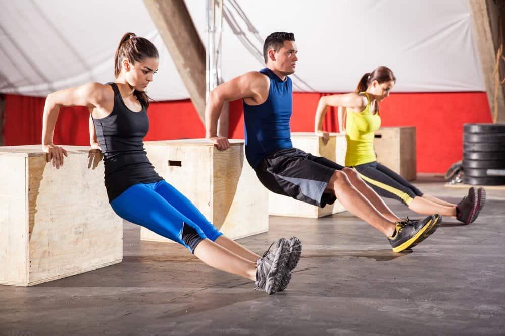 Young people exercising their arms using boxes in a cross-training gym - How to Boost Your Body's Fitness Level and Avoid The Risk of Injury. The Ultimate Guide in Cross-Training.