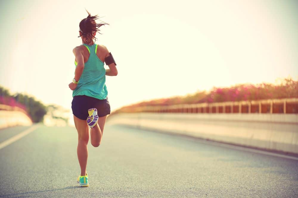 Young woman running on city road - How to avoid the risks of Running as a beginner and boost your body