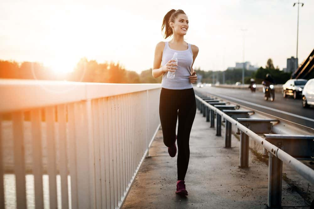 Young woman running over bridge - How Frequently Should a Beginner Exercise Running to Achieve Best Results for the Body and Avoid Injuries Explained