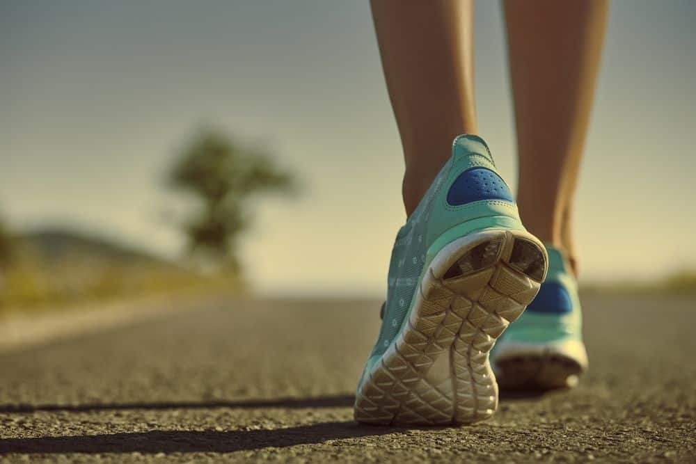 Athlete feet in running shoes jogging on the road - Running Gear for Beginners