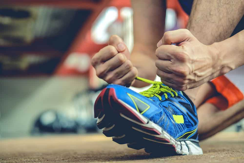 Athlete is tieing his shoelaces running shoes - Running Gear for Beginners