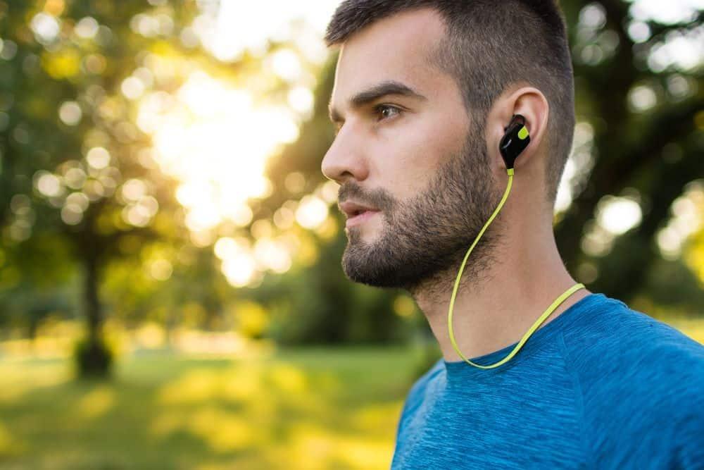 Closeup of a young runner wearing wireless headphones - Running Gear for Beginners