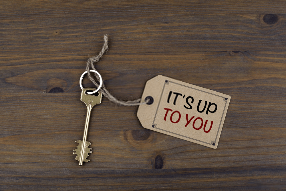 Key and a note on a wooden table - It's Up To You