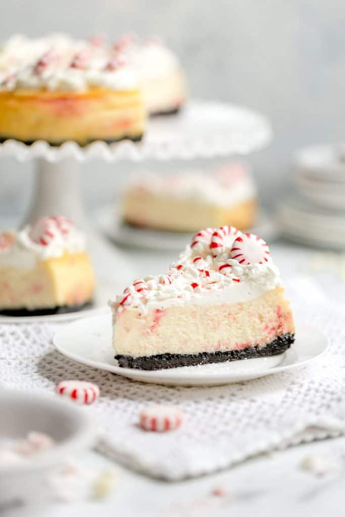 White Chocolate Peppermint Cheesecake - Smooth and creamy white chocolate cheesecake infused with cool peppermint flavor, a substantial chocolate cookie crust, and a cloud cover of whipped cream make this cheesecake recipe the holiday season's best, most beautiful dessert!