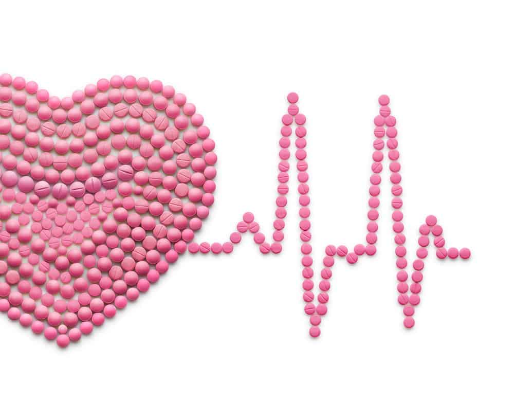 Creative medicine and healthcare concept made of drugs and pills, isolated on white. ECG, a human heart with a heartbeat line.