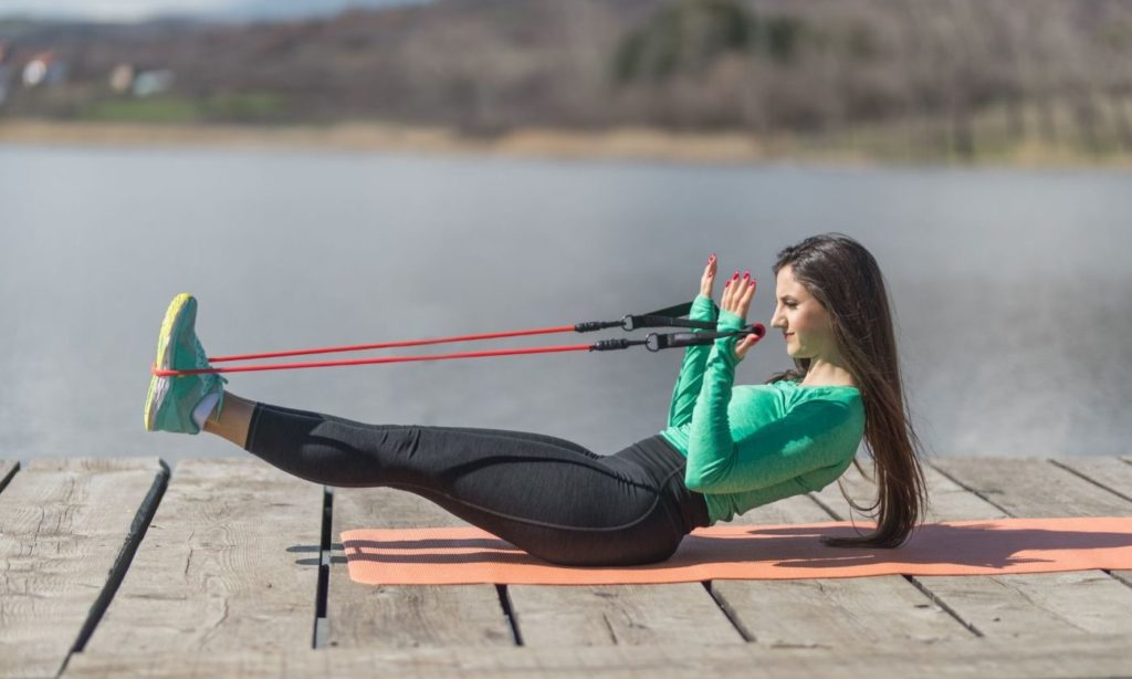 A young girl performing a resistance band workout session